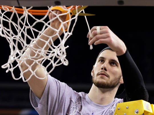 Duke's Brian Zoubek cuts the net after Duke's 61-59