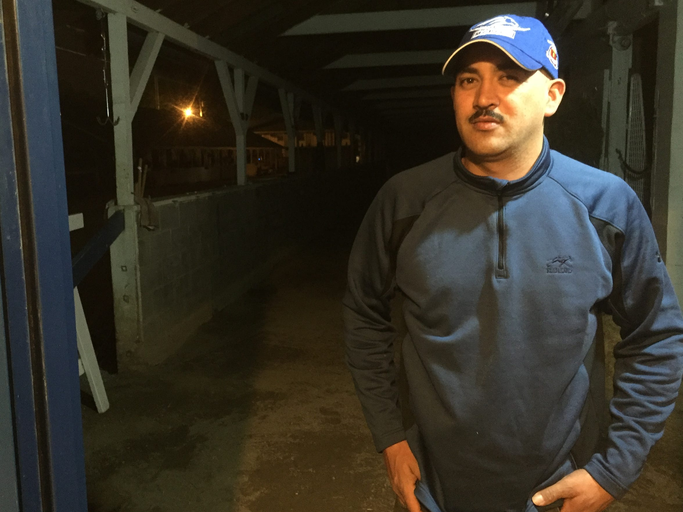 Marcos Abril stands in Barn 6 during the early morning