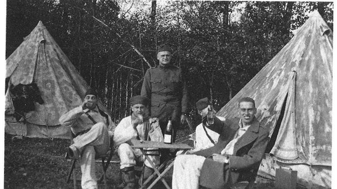 A moment of silliness at Soncamp, France. Enjoying what appears to be a Champagne breakfast are left to right, seated: pilots Leonard Desson, Howard Burdick, John Donoho (face hidden) by glass, Frank Dixon. The four are under the watchful eye of Dr. Jacob J. Ross of Middlebury.