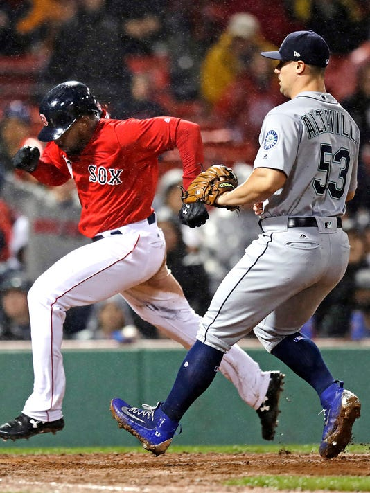 Boston Red Sox's Jackie Bradley Jr., left, scores on a bases-loaded wild pitch by Seattle Mariners relief pitcher Dan Altavilla (53) during the sixth inning of a baseball game at Fenway Park in Boston, Friday, May 26, 2017. (AP Photo/Charles Krupa)