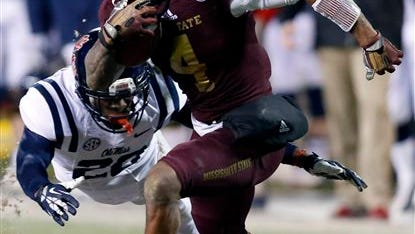 Mississippi State wide receiver Jameon Lewis (4) runs past Mississippi defensive back Carlos Davis (20) for a gain during the second half of an NCAA college football game, Thursday, Nov. 28, 2013, in Starkville, Miss. Mississippi State won in overtime, 17-10. (AP Photo/Rogelio V. Solis)