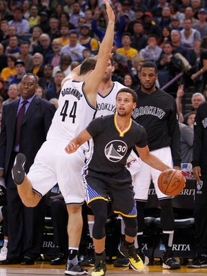Golden State Warriors guard Stephen Curry (30) dribbles the ball next to Brooklyn Nets guard Bojan Bogdanovic (44) in the first quarter at Oracle Arena.