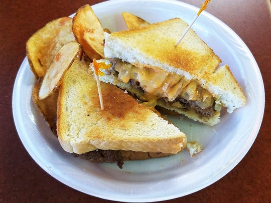 A patty melt at Freudenberg's is slathered in griddled onions and Thousand Island dressing and accompanied by house-fried thick chips.
