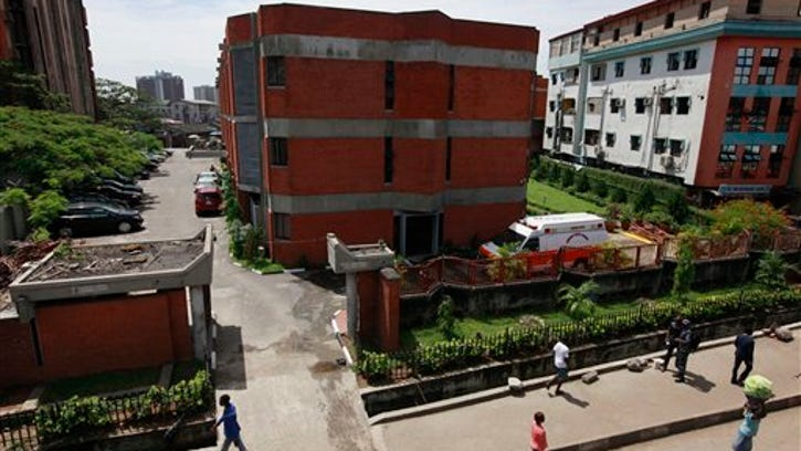 People walk past the First Consultant Hospital, were Liberian-American Patrick Sawyer, died in Lagos, Nigeria Monday.
