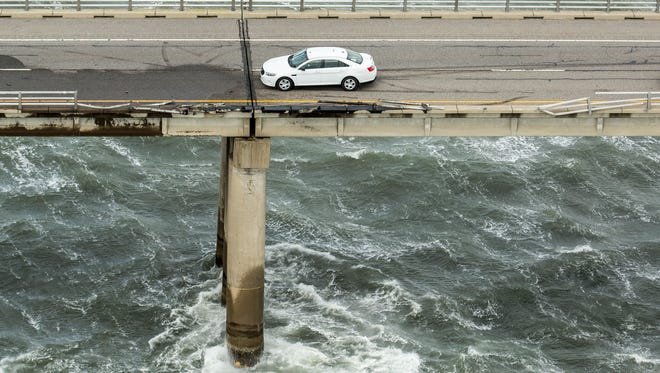 A vehicle sits on the road by a missing section of guard rail along a segment of the Chesapeake Bay Bridge-Tunnel where a tractor-trailer went over the southbound side at the 15-mile marker, Thursday afternoon Feb. 9, 2017, near Virginia Beach, Va. A truck driver died after heavy winds swept his tractor trailer off the 23-mile bridge-tunnel between Virginia Beach and the Delmarva Peninsula, and into the 45-degree, wind-swept waters below, authorities said. A Navy helicopter plucked a driver from the roof of the floating vehicle, but later died, authorities said. (Bill Tiernan/The Virginian-Pilot via AP)