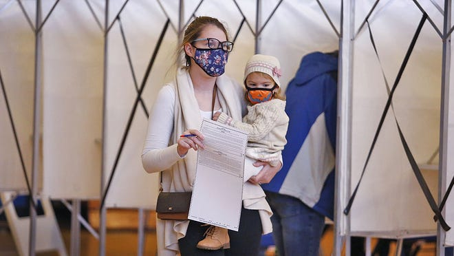 Randolph mom Olivia Francis with daughter Olivia, 2, after marking her ballot at Randolph High. Greg Derr/ The Patriot Ledger