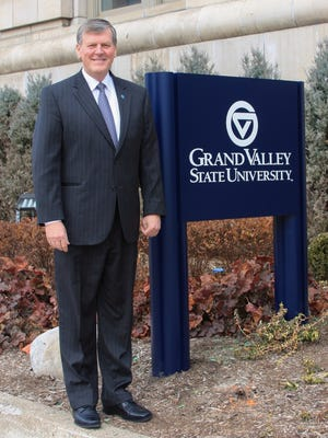 Grand Valley State University President Thomas Haas in front of sign for GVSU Charter School office in downtown Detroit.