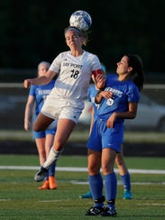 Bay Port's Anna Gulan (18) wins a header against Appleton West's Addie Pauling (15) in a WIAA soccer sectional semifinal.