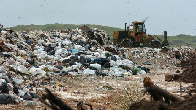 In this file photo, flies fill the air above the trash at Ordot dump before it was closed.