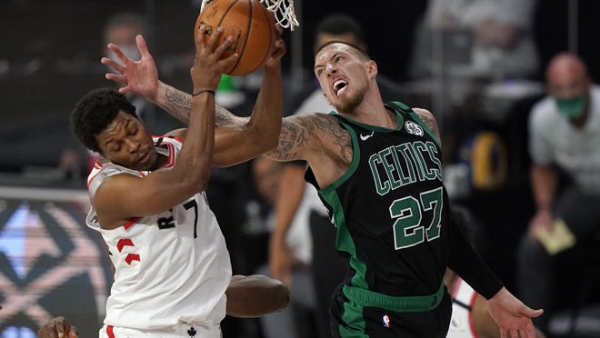 The Toronto Raptors' Kyle Lowry (7) grabs a rebound in front of the Boston Celtics' Daniel Theis (27) in the second half of an Eastern Conference semifinal game, Tuesday, Sept. 1, 2020, in Lake Buena Vista, Fla.