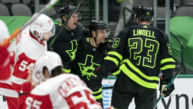 Dallas Stars' Denis Gurianov, left, Andrew Cogliano, center, and Esa Lindell (23) celebrate Cogliano's goal against the Detroit Red Wings during the second period of an NHL hockey game Thursday, Jan. 28, 2021, in Dallas.