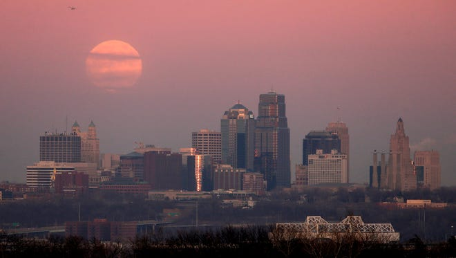 A full moon is shrouded in haze as it rises over the Kansas City, Mo. skyline at sunset Monday, Dec. 16, 2013.