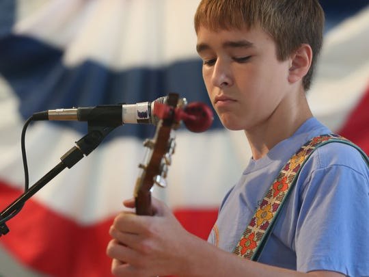 Grayson Cox, 15, of North English plays his banjo at Pioneer Hall during The Iowa State Fair Sunday, Aug. 10, 2014.