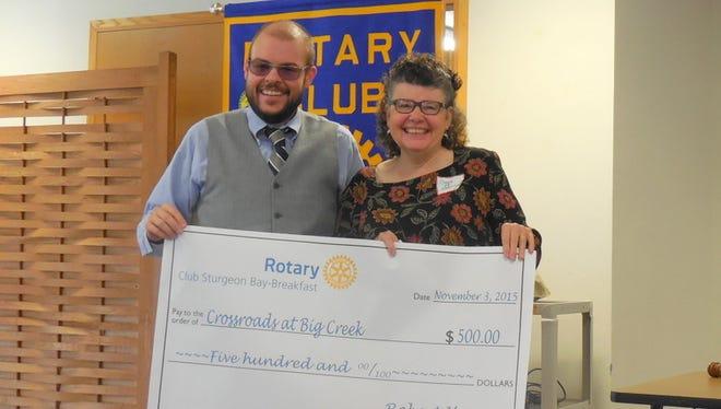 Bill Kletzien, president-elect of Breakfast Rotary, presents $500 check to Coggin Heeringa, executive director, Crossroads at Big Creek