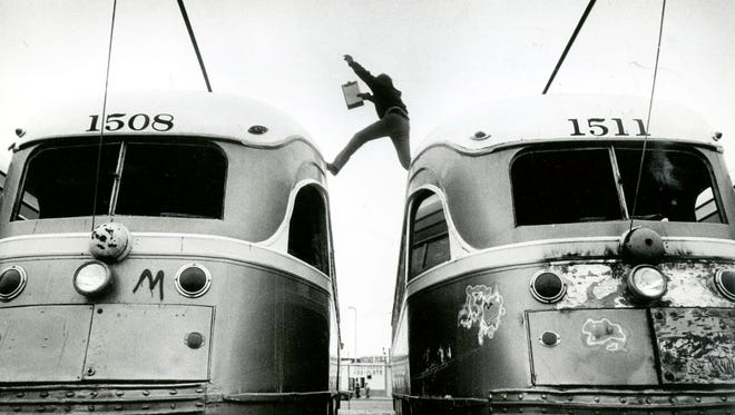 R.L. Thomas, a volunteer for the Del Norte Streetcar Preservation Society, leaps across streetcars as he inspects them for damage.