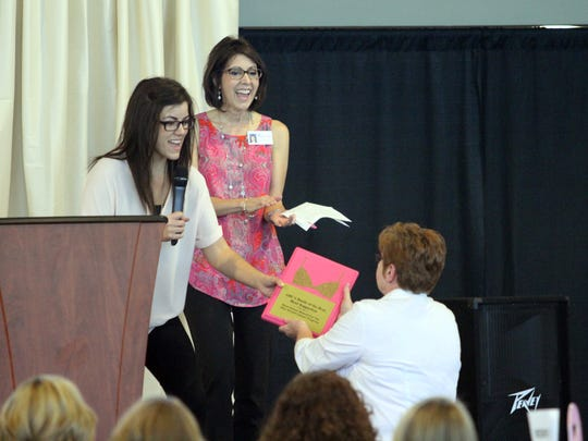 Jessica Goldberg, left, and Benita Martin present a plaque to Premiere Medical Group, one of the winners of this year's Battle of the Bras, at the annual Tickle Me Pink luncheon.