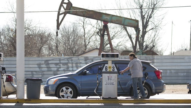 A motorist fills her car with gas at a gas station near an oil field pumping rig Feb. 12, 2016 in Oklahoma City.   (Photo by J Pat Carter/Getty Images)