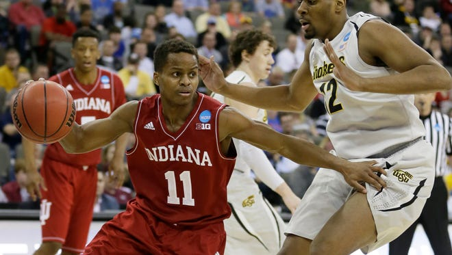 Indiana guard Yogi Ferrell, left, drives past Wichita State forward Darius Carter during the first half of an NCAA tournament in the Round of 64, March 20, 2015, in Omaha, Neb.