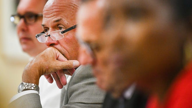 Sitting with Peoria City Council members, Peoria Mayor Jim Ardis stares over his glasses during a council meeting.