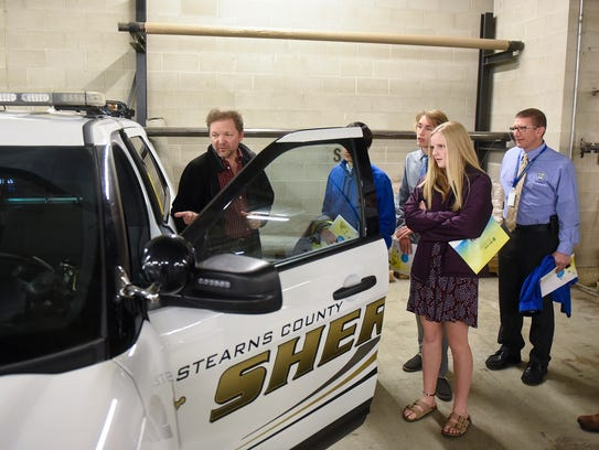 Cathedral High School students learn about technology installed in county squad cars during a tour Tuesday, Oct. 17, in St. Cloud.