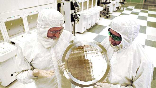 Dr. Michael Liehr (left) of SUNY Poly CNSE and Bala Haran of IBM Research inspect a wafer comprised of 7nm (nanometer) node test chips in a clean room in Albany, NY.