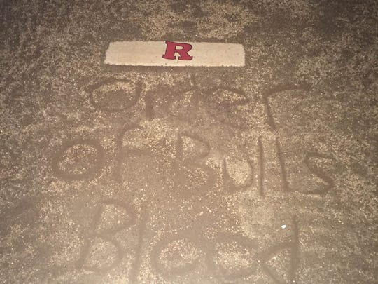 """Order of Bulls Blood"" written in what appears to be sand below the Rutgers logo."