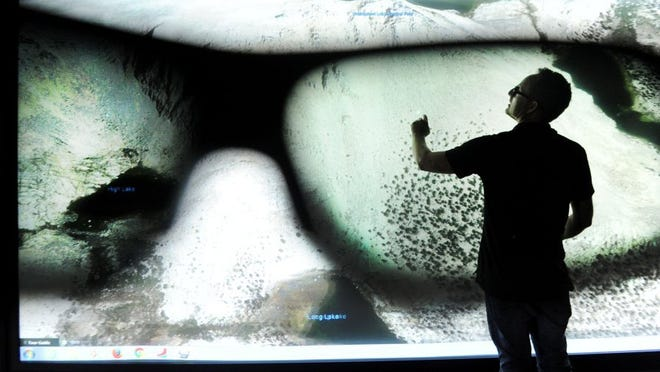 Grant Jones, IT director for Ventura College, shows a rear projection touch screen in this photo taken through 3D glasses. The screen, 20 feet wide and 7 feet high, is in Ventura College's new Applied Science Center. The image on the screen is of Lone Pine.