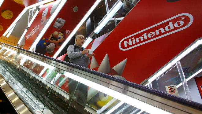 In this March 20, 2016 file photo, a shopper on an escalator passes by the Nintendo logo at an electronics store in Tokyo.