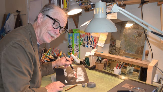 Jerry Pope works in his home study, accompanied by an arsenal of pointed colored pencils and a sharp wit.