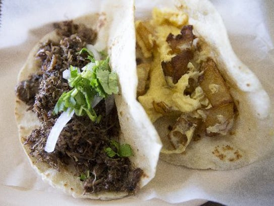 This barbacoa taco and egg and potato taco are two