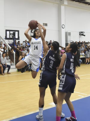 The St. Paul Christian Warriors' Joylyn Pangilinan (14) takes a jump shot against the Academy of Our lady of Guam Cougars during their Independent Interscholastic Athletic Association of Guam Girls Basketball League game at St. Paul Christian School gym in Dededo on Nov. 14.