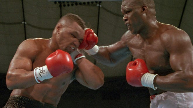"In this Feb. 11, 1990, file photo, James ""Buster'' Douglas, right, hits Mike Tyson with a hard right in the face during their world heavyweight title bout at the Tokyo Dome in Tokyo. It's been 25 years since one of the most stunning upsets in sports history."