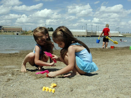 Children play at Saxony Beach. The beach features a swimming area and boat rentals.