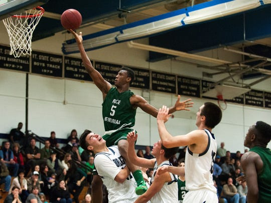 Rice's Kendrick Gray (5) leaps over Burlington's Asmin Mostarlic (12) for a layup during the boys basketball game between the Rice Green Knights and the Burlington Seahorses on Dec. 9, 2014.