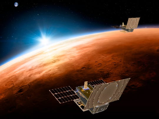This illustration made available by NASA shows the twin Mars Cube One spacecraft flying over Mars with Earth and the sun in the distance. The devices will be the first CubeSats - a kind of modular, mini-satellite - flown into deep space. They're designed to fly along behind NASA's InSight lander on its cruise to Mars.