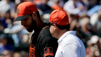 Giants starting pitcher Madison Bumgarner, left, leaves the field after getting hit by comebacker during the third inning.