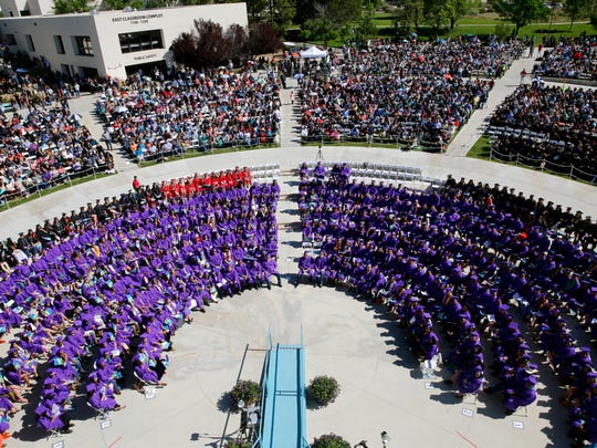 San Juan College graduates, along with graduates from the Farmington locations of  New Mexico Highlands University and the University of New Mexico, listen to guest speaker Andrew Thompson speak in the Learning Commons Plaza on Saturday.