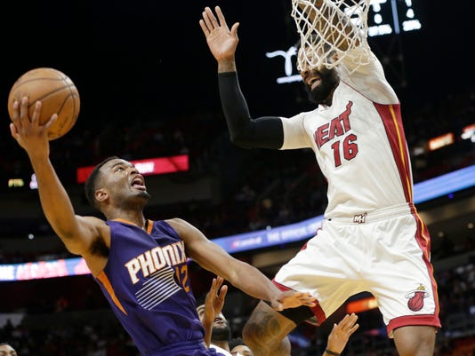Phoenix Suns' TJ Warren (12) drives to the basket as Miami Heat's James Johnson (16) defends during the first half of an NBA basketball game, Tuesday, March 21, 2017, in Miami. (AP Photo/Lynne Sladky)
