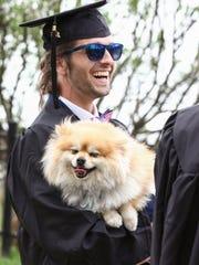 Graduating senior Neal Pavlak with his dog Mufasa walk