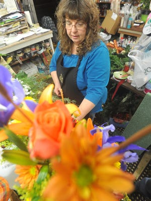 Colleen Turner creates a floral arrangement on Monday at Bellville Flowers & Gifts, 72 Main St.