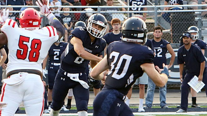 Greenwood's Jace Presley throws over Forth Smith Northside's defense Friday, Sept. 6, 2019, as now-head coach Chris Young (right) watches from the sideline during first-quarter play at Smith-Robinson Stadium last season.