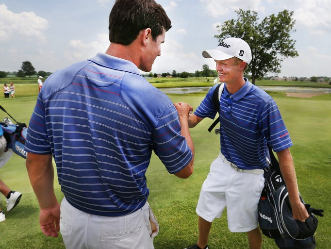 Columbus North's Christian Fairbanks, left, teammate Michael VanDeventer fist bump on the 18th hole at The Legends Golf Club in Franklin on Wed. June 18, 2014 after finishing tied for first in the individual high school state finals and leading the Bulldogs to the school's first state golf title since 1934.