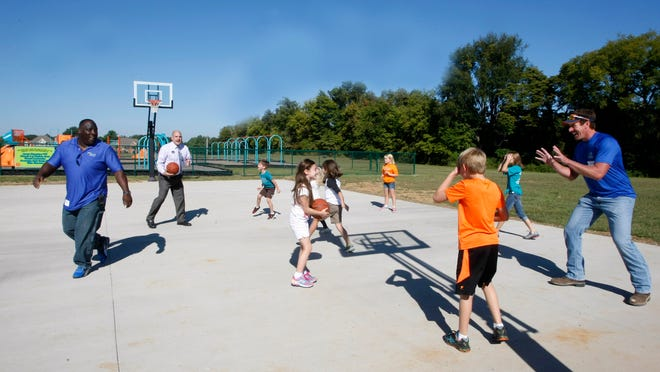 Duane King, left, David Blevins and Marty Darnell play around of ball with some Carmel Elementary students on the new basketball court they help build at the school.