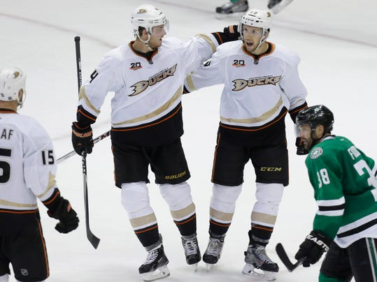 Anaheim Ducks center Nick Bonino (13) right celebrates scoring a goal with teammate Cam Fowler (4) during the third period of Game 6 of a first-round NHL hockey playoff series against the Dallas Stars in Dallas, Sunday, April 27, 2014. The Ducks won 5-4 in overtime. Looking on are Ducks Ryan Getzlaf (15) and Stars Vernon Fiddler (38). (AP Photo/LM Otero)