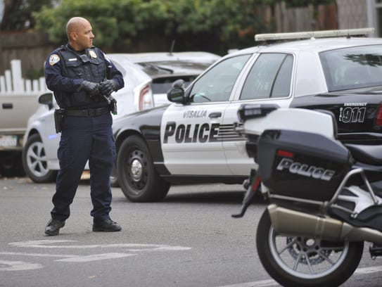Officer Adam Aguallo directs traffic while police searched