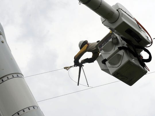 Standing in a bucket high above the ground, Josh Blackburn of Shenandoah Valley Electric Cooperative works on utility lines along Middlebrook Road on Sunday, July 1, 2012. Crews continue to work to restore power in the wake of Friday night's storm.