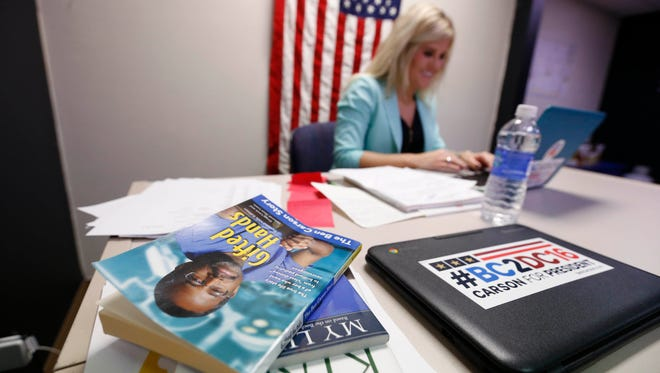 Megan Assman, a staff member with Republican presidential candidate Ben Carson's campaign, looks up phone numbers of supporters to call Tuesday, Dec. 15, 2015, at the campaign's office in Urbandale.