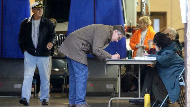 Allen Foster (left) leaves a voting booth while Nick Wasileski signs in before voting in the Newark city elections at District 3's polling site at Aetna fire station.