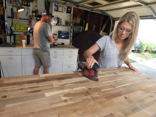 Mary Catherine Kreamer sands the top of a bar that she and her husband Dan are making in their garage.