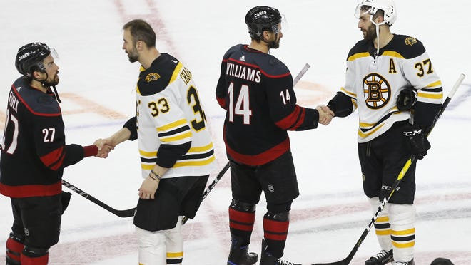 Carolina Hurricanes defenseman Justin Faulk (27) and Hurricanes right wing Justin Williams (14) congratulate Boston Bruins defenseman Zdeno Chara (33) and Bruins center Patrice Bergeron (37) in the handshake line after their game in game four of the Eastern Conference Final of the 2019 Stanley Cup Playoffs at PNC Arena.